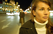 Young woman walking in street at night