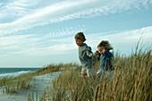 Boy and girl running through dune grass, holding hands