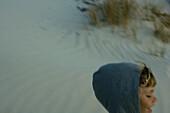 Child wearing hooded sweatshirt on dune, cropped