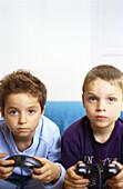 Two boys sitting on sofa holding joysticks