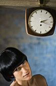 Woman beneath clock, head and shoulders
