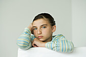 Preteen girl resting head on hand, looking at camera