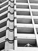 Facade of apartment building, person leaning against railing, b&w