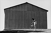 Woman watering ground with watering can behind warehouse, b&w