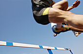 Athlete jumping hurdle, low angle view