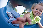 Close-up of girl reaching for camera, lying in playground tunnel