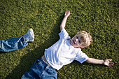 Boy lying on grass, high angle view