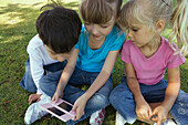 Three children sitting on grass, playing with video game, close-up