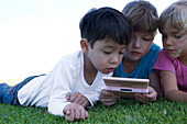 Three children lying on grass, playing with video game, close-up