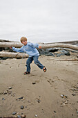Young Boy Throwing Rocks on Beach, Oregon, USA