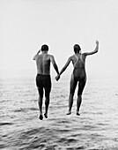 Couple Holding Hands While Jumping Into Water