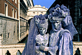 Couple in carneval costume in front of the Bridge of Sighs, Ponte dei Sospiri, carnival, Venice, Italy
