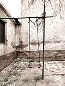 Deserted backyard, children's swing, Minas de Alquife, Andalusia, Spain