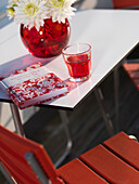 Modern decorated garden table with red book and red drink, Kolbermoor, Bavaria, Germany