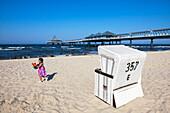 Little girl with beach toys, beach chair and pier, Heringsdorf, Usedom island, Baltic Sea, Mecklenburg-West Pomerania, Germany