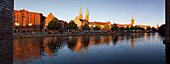 Panoramic view over the Trave river to the old town of Luebeck with old storehouses at the Holsten harbour, St Mary´s church and church of St Petri, Hanseatic city of Luebeck, Baltic Sea, Schleswig-Holstein, Germany
