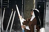France, Lourdes, Nun lighting a candle at the Lourdes shrine