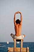 Cape Verde Peninsula, Sal, Santa Maria beach, teen boy in yoga attitude