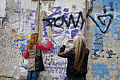 Germany, Berlin, Friedrichshain, East Side Gallery, woman writing on the Wall