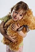 Little girl holding a teddy bear, studio