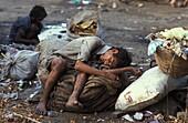 Inde, Maharastra, Mumbai, Scavenger stoned on glue sleeping on a garbage bag