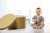 Smiling baby boy sitting on floor, next to box
