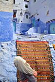 Alte Frau vor Teppich und Gasse mit blau bemalte Häusern in Chefchaouen, Riff Gebirge, Marokko, Afrika