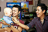 Two young Thai guys playing with a German baby in a bar, Pai, Thailand, Asia