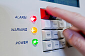 Hand pushing button on alarm system, Germany