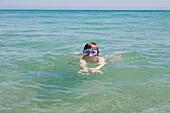 Boy with diving goggles swimming in Atlantic Ocean, Costa Calma, Fuerteventura, Canary Islands, Spain
