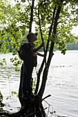 Junge steht auf einem Baum am Seeufer, Lankau, Schleswig-Holstein, Deutschland
