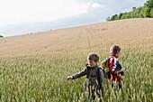 Two boys in grain field, Lankau, Schleswig-Holstein, Germany