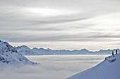 Two people enjoying mountain panorama over clouds, Hahnenkamm, Kitzbuehel, Tyrol, Austria
