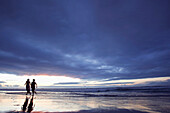 Couple walking along beach in twilight, Fuerteventura, Spain