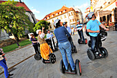 People on segways during a guided tour at the old town of Bratislava, Slovakia, Europe