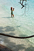 Asian tourist barefoot in the sea using a video camera, Similan Islands, Andaman Sea, Thailand