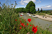 Boats on the canal du Midi with two cyclists cycling past, Beziers, Midi, France