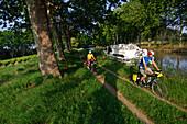 Cyclists cycling past a boat, Canal du Midi, Midi, France