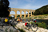 Cyclists having a rest near the aquaduct, Pont du Gard, Provence, France