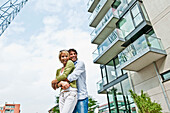 Couple embracing near modern apartment building, HafenCity, Hamburg, Germany