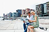 Paar mit einem Stadtplan an den Magellan-Terrassen, HafenCity, Hamburg, Deutschland