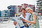 Couple holding a city map at Magellan-Terraces, HafenCity, Hamburg, Germany