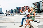 Couple reading a city map at Magellan-Terraces, HafenCity, Hamburg, Germany