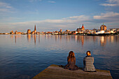Two women sitting on a landing stage, view over Warnow river to the Old Town and St Mary´s church, Rostock, Baltic Sea, Mecklenburg Western-Pomerania, Germany, Europe