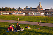 People having picnic at the Elbe river, Bruehlsche Terrasse and Frauenkirche in the background, Dresden, Saxonia, Germany, Europe