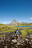 Woman hiking near lake Lac d'Ayous, Pic du Midi d'Ossau in background, Ossau Valley, French Pyrenees, Pyrenees-Atlantiques, Aquitaine, France