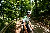 Radrennfahrer blickt nach hinten, Bergisches Land, Nordrhein-Westfalen, Deutschland
