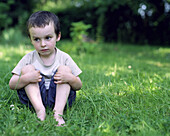 Little boy sitting in grass, looking away in thought