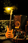 Bass guitar and amplifier set up outdoors for nighttime performance