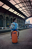 Little girl sitting on suitcase waiting in train station
